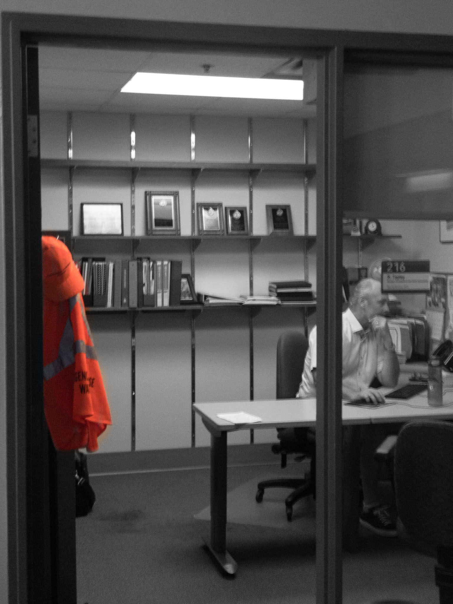Image of a person at their desk with an emergency response warden hat and vest in the forground